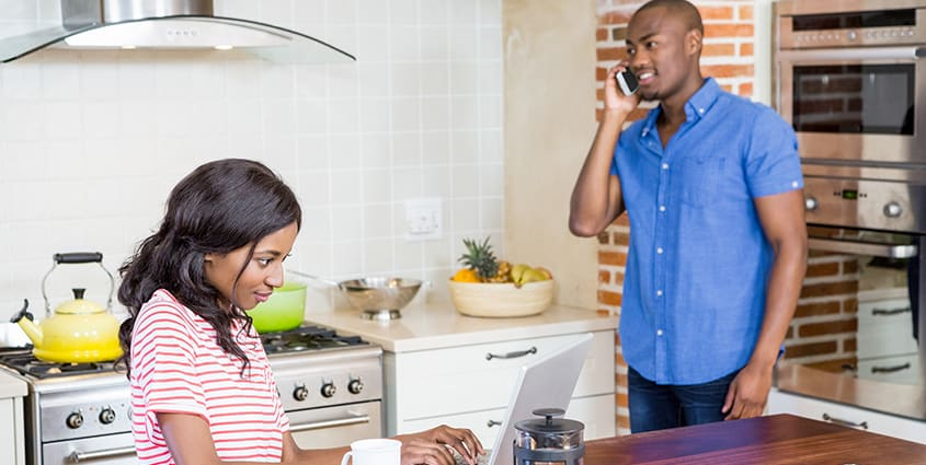 Couple in kitchen on devices