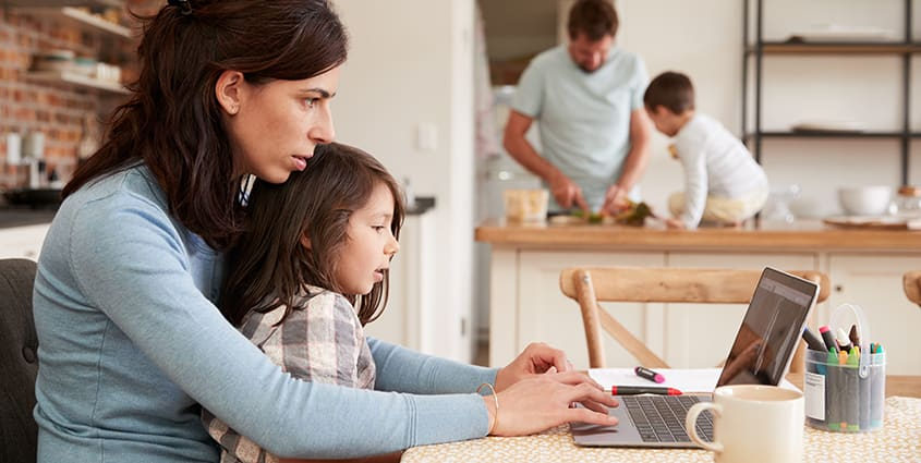 Family in kitchen cooking and using computer