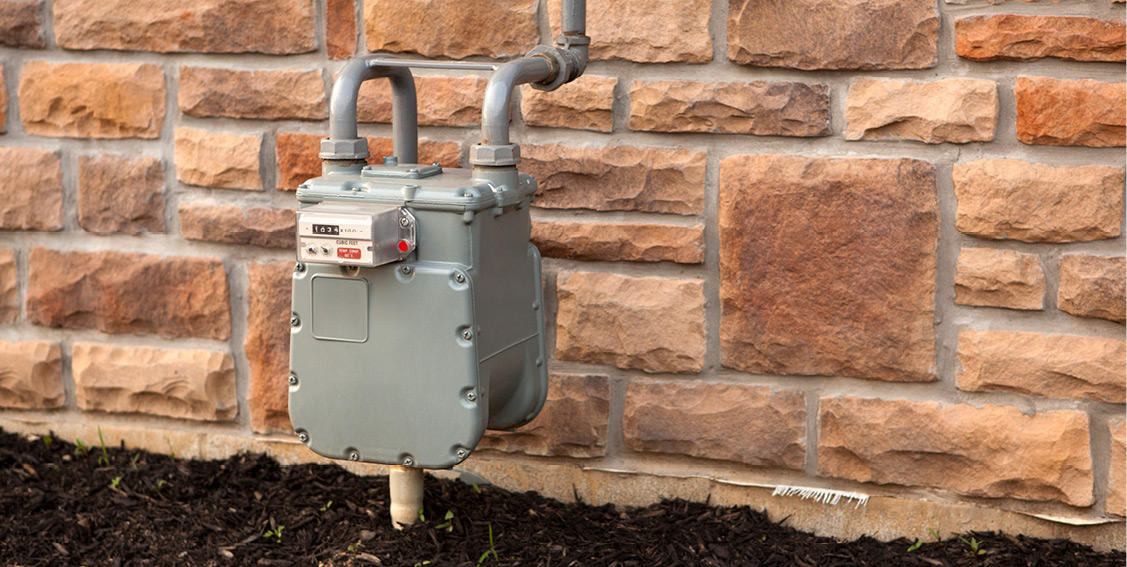 Natural gas meter against the side of a stone wall