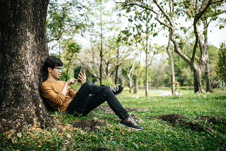 Guy on device under a tree