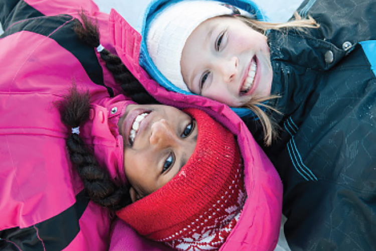 Two young girls in snow in winter coats