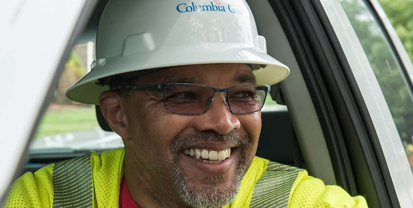 African American male Columbia Gas employee smiling wearing white hard had with Columbia gas logo