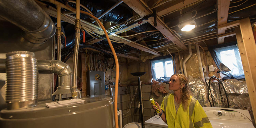 Employee looking at natural gas lines in customer home