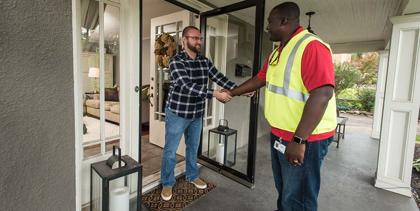 African American employee shaking hands with customer in flannel shirt as he leaves home after service