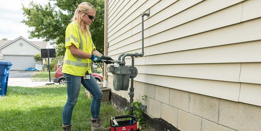 Female employee  working at a gas meter on the side of a house that has beige siding