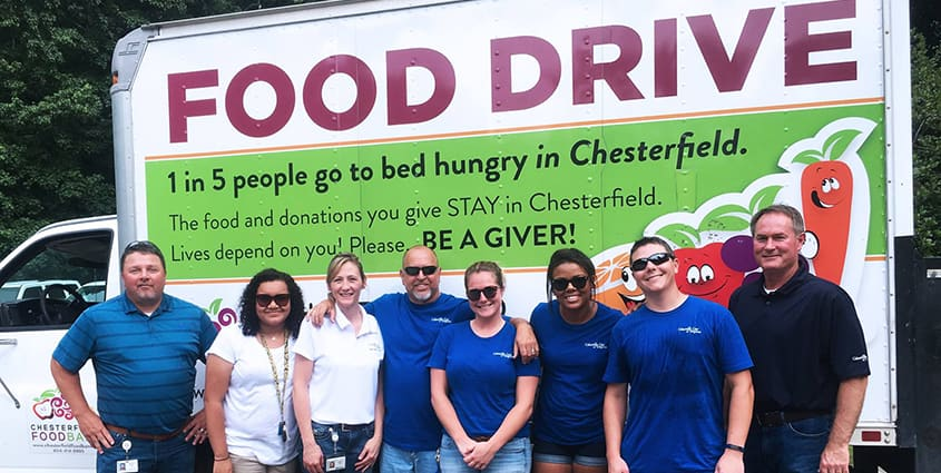 Columbia Gas employees standing in front of a food drive truck after volunteering