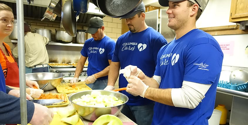 3 male employees with blue Columbia Cares volunteer shirt volunteering at soup kitchen