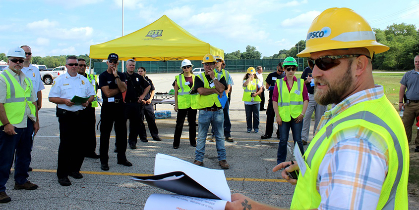 NIPSCO employees meeting outside with some employees wearing hard hats with NIPSCO logo