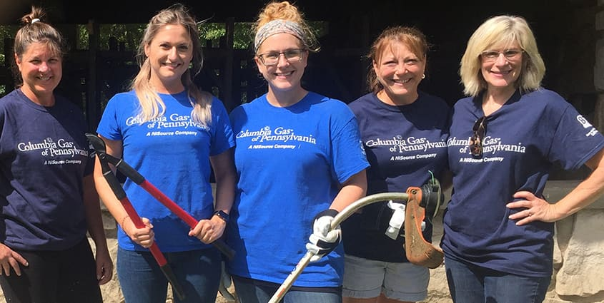Pennsylvania employees wearing Columbia Gas volunteer shirts and holding up garden tools