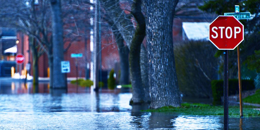 Deep water in flooded streets covering bottom of a stop sign at front of photo, large trees