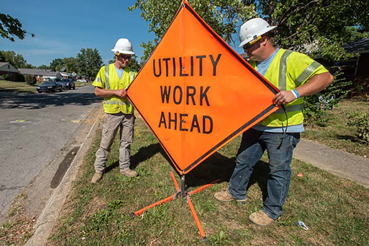 Construction workers holding sign that reads utility work ahead