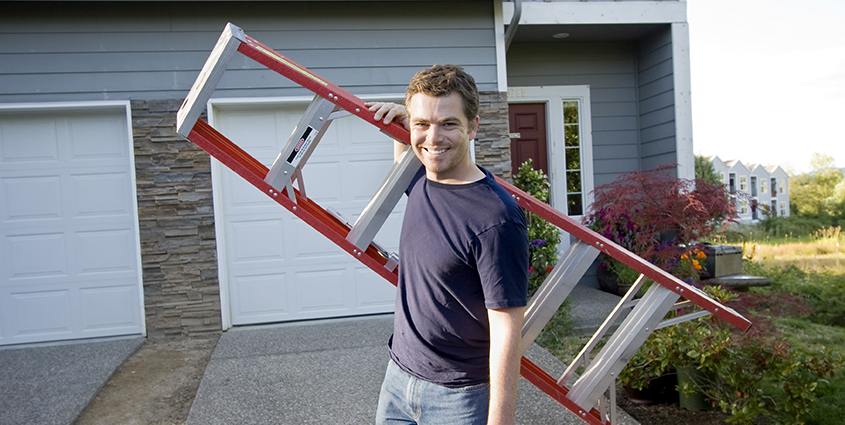 Man carrying ladder outside