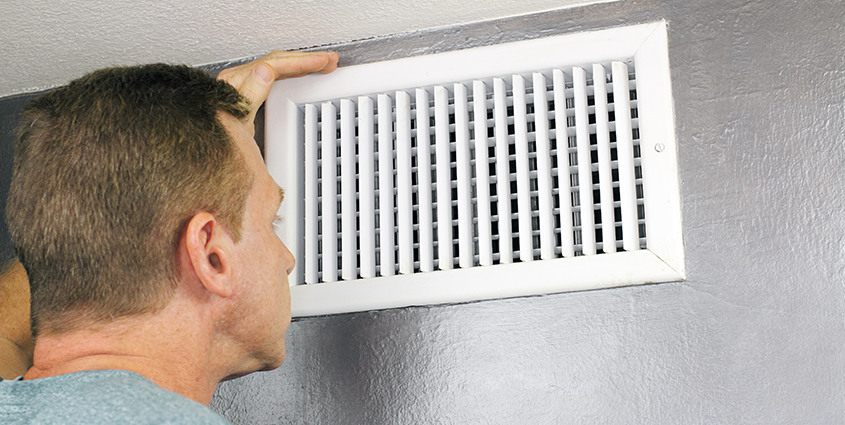 Man looking at venting in home